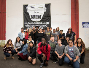 The students in the Portland History class who organized the event with one of their posters.
